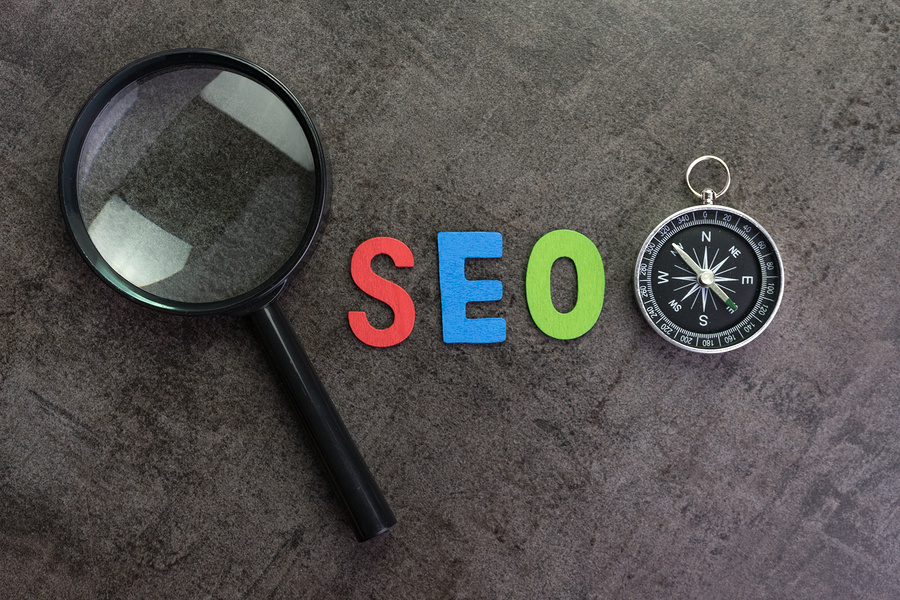 Magnifier Glass, Colorful Alphabet Seo And Compass On Dark Chalk